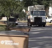 A garbage truck prepares to pick up trash on a city street