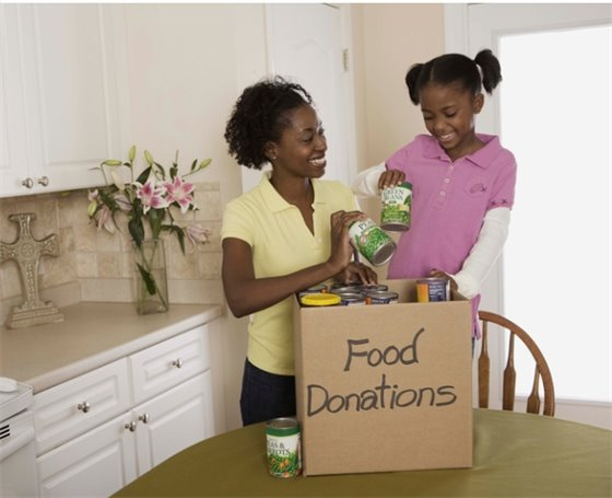 A woman and her daughter put food cans in a box