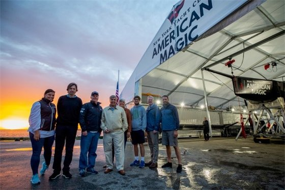 A group photo in front of the American Magic boat