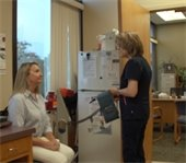 Two woman look at each other at a nurse station