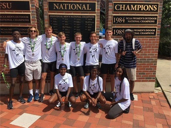 Group of runners poses with medals from regional running club