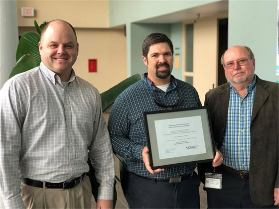 City staff pose with a framed certificate