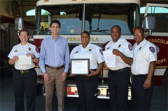 Jamie Beckham presents a $2,500 fire prevention grant to Pensacola Fire Department on behalf of FM Global.