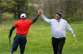 Two veterans high-fiving on the golf course.