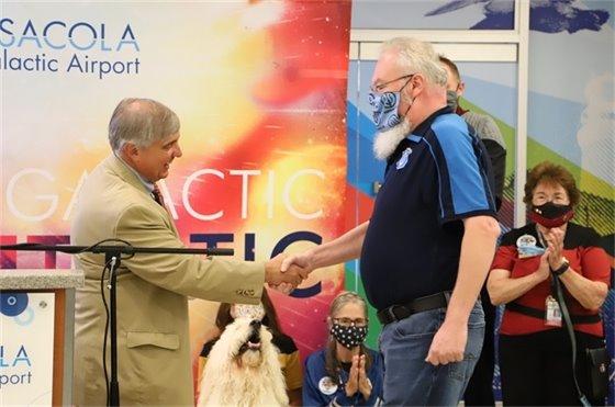 Mayor Grover Robinson shakes Mike Ensley's hand at Pensacola International Airport