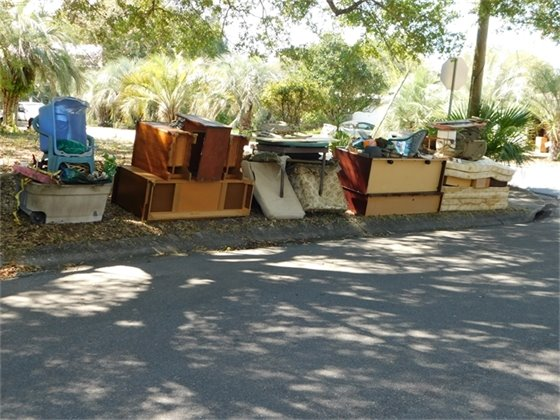 Before image of piles of bulk items ready for the neighborhood cleanup.