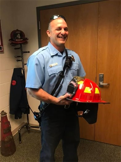 a photo of a firefighter holding a helmet