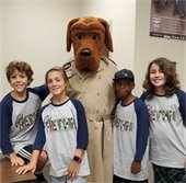 Kids pose with a dog at Camp Friendship