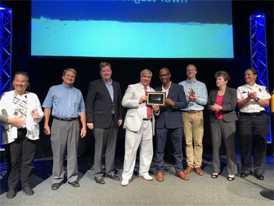 Elected officials hold the Strongest Town 2019 award on stage
