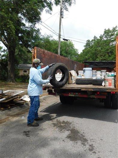 City Sanitation staff loads bulk waste into a truck trailer.