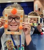 Kids participating in PPD Camp Friendship hold up picture frames they made