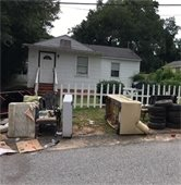 House with tires and debris in front of it