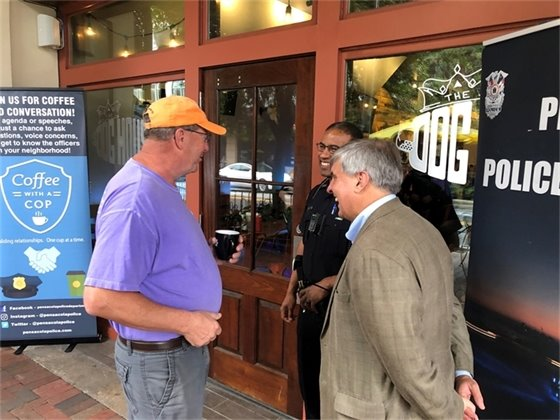 Mayor and cop laugh with a citizen in front of dog house deli
