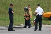 Three people stand by a person in firefighting gear