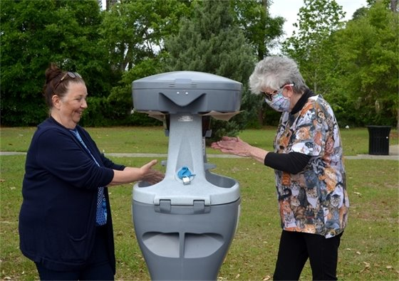 Councilwoman Ann Hill and Councilwoman Sherri Myers test out the portable hand-washing station at Bryan Park.