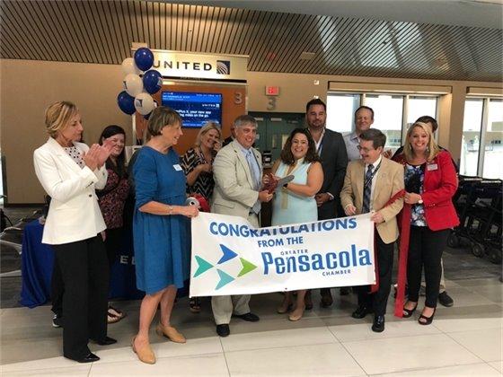 Mayor Grover Robinson cuts the ribbon at the inaugural Newark flight celebration at Pensacola International Airport