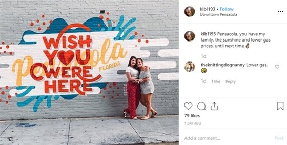 "two girls stand by a mural that says ""wish you were here"""