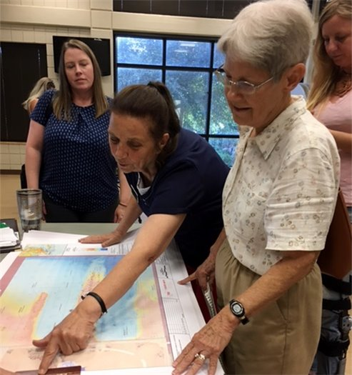 Several women look at map of the project