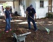 Workers rake yard debris