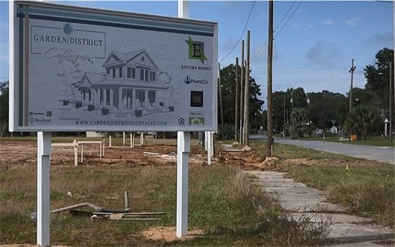 Photo of a sign showing a rendering of Garden District Cottages