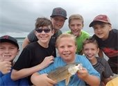 A group photo of kids holding a fish