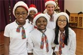 A group photo of children wearing santa hats