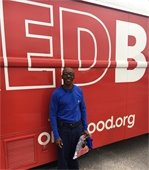 A man standing by the bloodmobile