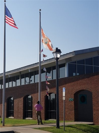 Man raises flags on flag staff