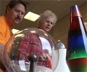 two people stand by a lava lamp