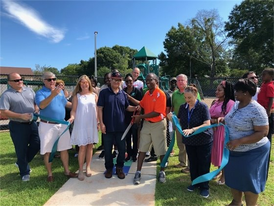 A group cuts a ribbon to celebrate the Morris Court Park reopening