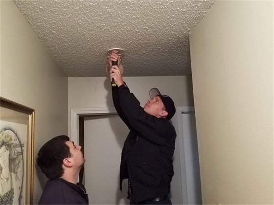 Firefighters install a smoke alarm in a home