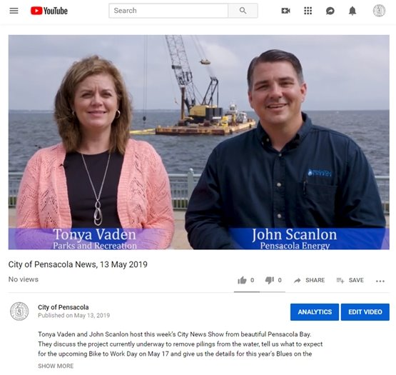 A photo of Tonya Vaden and John Scanlon sitting in front of a crane barge