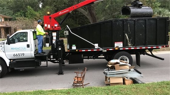 City sanitation worker picks up debris with a truck