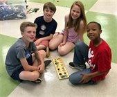 kids sitting around a board game