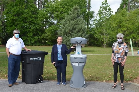 Mayor Grover Robinson, Councilwoman Ann Hill and Councilwoman Sherri Myers pose with a portable hand-washing station at Bryan Park.