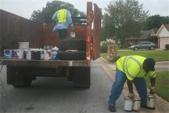 Crews pick up paint cans during a mayor's neighborhood cleanup