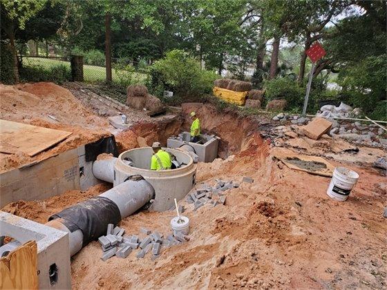 Crews work on installing an underground stormwater treatment unit