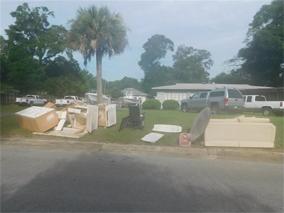 Yard full of disposed furniture and cabinets before pickup.
