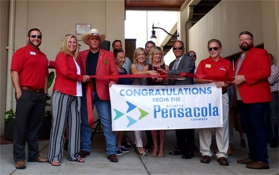 "Group of people hold banner that says ""congratulations from the pensacola chambre"""