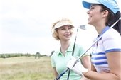 Two women who are holding golf clubs and smiling