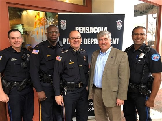 Mayor poses outside of Coffee with a Cop event with several city police officers.