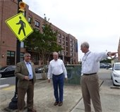 Three people stand at a crosswalk with a pedestrian sign