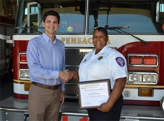Jamie Beckham presents a $2,500 fire prevention grant to Fire Marshal Annie Bloxson on behalf of FM Global.