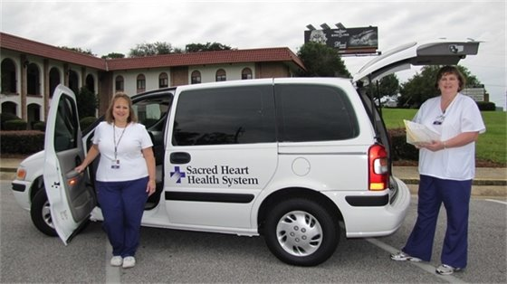 sacred heart doctors stand next to a health van