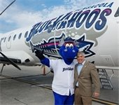 Mayor Robinson with Kazoo in front of a plan with a blue wahoos wrap