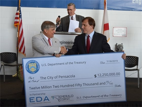Mayor Grover Robinson accepts a $12.25 million check from Dr. John Fleming, Assistant Secretary of Commerce for Economic Development