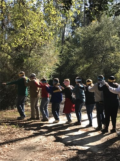 City staff lead each other blindfolded in the woods