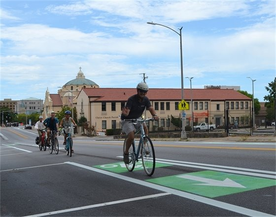 People ride bikes down the new bike lanes along Palafox Street