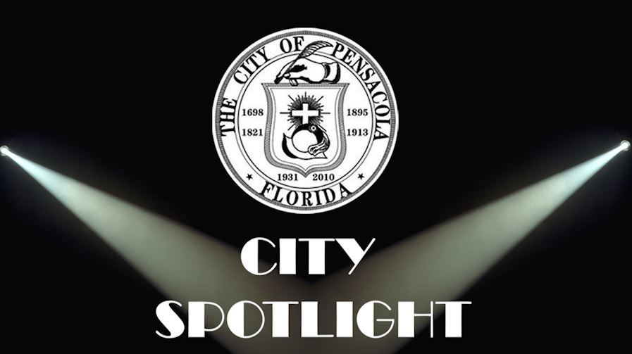 the seal of Pensacola and a spotlight