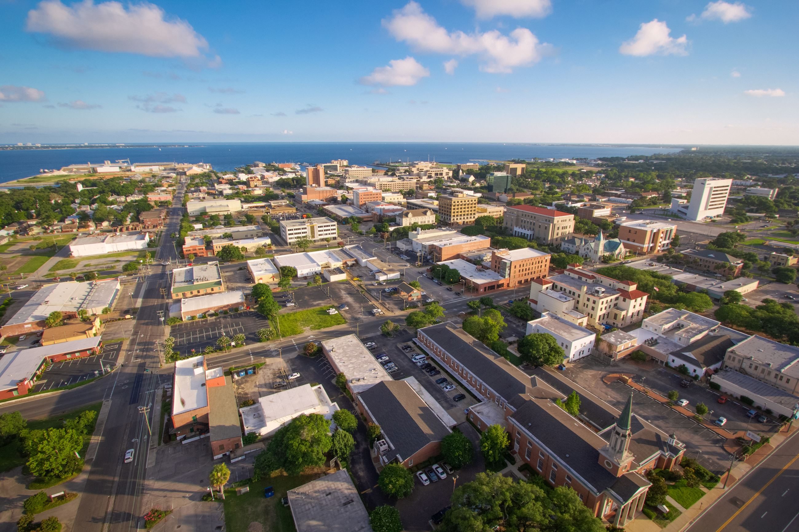 Aerial of businesses and buildings in downtown Pensacola with bay in background